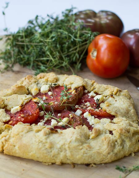Tomato Galette on wood cutting board with fresh thyme and tomatoes in background.