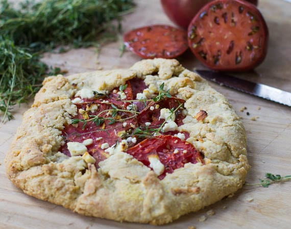 Tomato Galette with Feta with fresh thyme and tomatoes in background.