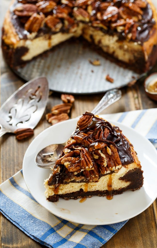 Turtle Brownie Cheesecake with a brownie crust and pecans, caramel sauce, and chocolate sauce on top.