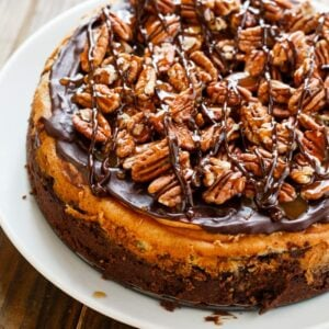 Turtle Brownie Cheesecake with a brownie crust and pecans, caramel sauce, and chocolate sauce.