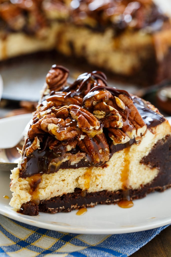 Turtle Brownie Cheesecake with a brownie crust, and pecans, caramel sauce and chocolate sauce on top.