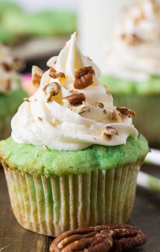Watergate Cupcakes flavored with pistachio pudding and pineapple. Topped with marshmallow fluff frosting.